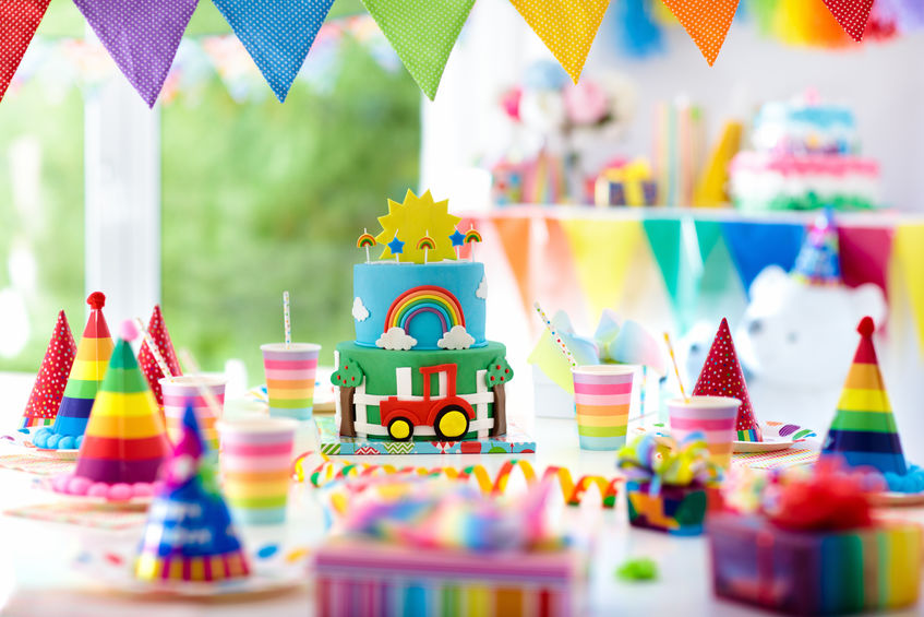 Kids birthday party decoration. Colorful cake with candles. Farm and transportation theme boys party. Decorated table for child birthday celebration. Rainbow cake for little boy. Balloons and banners.